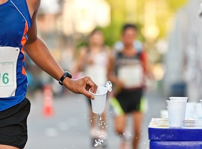 Runner grabs cup of watter