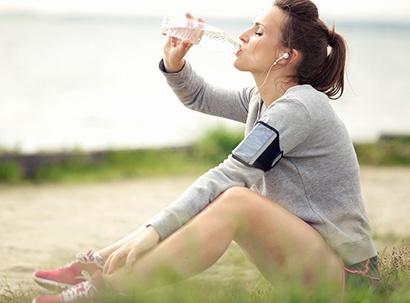 Woman drinks Eldorado water while taking a break from exercising