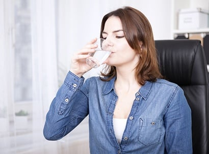 Lady drinks glass of water